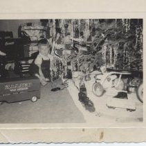 Image of Boy by Christmas Tree with Toy Trains and Allied Van Lines Truck - Young boy sitting by Christmas tree with tricycle, Allied Van Lines truck and toy trains.