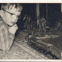 Image of Boy in Glasses on Floor with Toy Trains - German photo of young boy in glasses playing on floor with toy train on track.  See also P2007.348.001 and P2007.341.001 for other photos of the same layout.