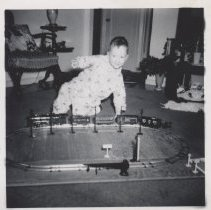 Image of Small Boy in Pajamas Plays with Train Set on Floor - Photo of small boy in pajamas playing witb toy trains with telegraph poles.