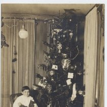 Image of Young Boy Sits on Wicker Chair at Christmas - Photo of young boy sitting in wicker chair beside Christmas tree.  No trains but many toys in photo.