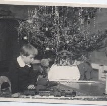 Image of German Boy Plays with Toy Trains at Christmas - Photo from 1910 era.  Karlsruhe, Germany.  Little boy in white color plays with toy trains on floor at Christmas