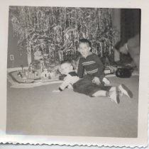 Image of Two Boys with Lionel Freight Set under Christmas Tree - Christmas photo.  Two boys in front of Christmas tree.  One  has his mouth wide open and one is lying on his stomach.  Under tree is Lionel ABA freight set with Plasticville buildings.  See also 001, 002 & 004.