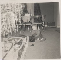 Image of Small Boy under Christmas Tree with Lionel ABA Freight Set - Christmas photo.  Small boy sits under Christmas tree.  Around the tree runs a Lionel ABA freight set with operating milk car.  Plasticville  buildings around set.    See also 001, 002 & 003.