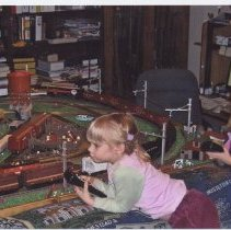 Image of Grandaughters Operate Grandfather's Layout - 2 small grandaughters of TCA member, John Fullerton, operate his toy train layout.  Lionel water tower with scratch built stock pens.  A mix of MTH, Weaver, Lionel, K-line and Atlas rolling stock.