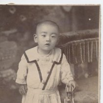 Image of Japanese Child with Wooden Toy Train - Toddler holds (wooden?) toy train wearing a white dress.