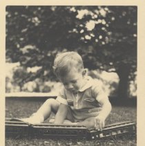 Image of Young Boy Plays with Cast Iron Toy Train - Very young boy sits outdoors in grass, playing with cast iron toy train passenger cars.