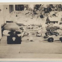 Image of Toys Under Christmas Tree - Toy train, roadster, airplane, truck and Lincoln Log house under Christmas tree.  Image is indistinct.