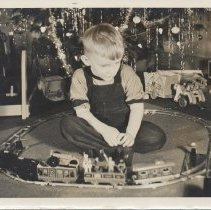 Image of Boy at Christmas with Marx Train Set - Young boy in overalls sits under Christmas tree inside circle of track with Marx train set.  This is a Marx No. 540 train set.  This photo does not show the tank car or tender that would be a part of the complete set.  Marx gondola #552 CRI&P, Marx hopper #554 NP, Marx caboose #556, Marx sparkling clockwork Commadore Vanderbuilt (no number) and Marx manual switches. Research by Jim Yocum.