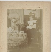 Image of Child with Toy Pony and Cast Iron Toy Train - Photo of young child in white collared shirt sits on chair, holding the reigns of toy pony.  Cast iron toy train on table?  Train is made by Ideal, circa 1894.  Nickel plated locomotive and two nickel plated coaches.