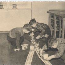 Image of Three Boys Play on Floor with Wooden Train Set - German photo of 3 young boys playing with a wooden train set.
