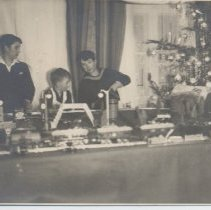 Image of Large European Christmas Layout - Three young boys stand behind large layout with buildings and tunnel.  Christmas tree in background.