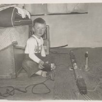 Image of Christmas 1951, Boy Plays with Lionel Trains - Photo of  young boy in suspenders playing with Lionel train set and transformer on floor Christmas day.