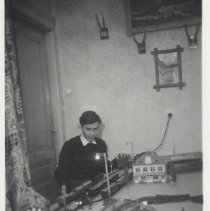 Image of Boy with Layout and European Station - German photo?  Teenage boy stands by toy train layout on table.  Marklin or Bing station on layout.