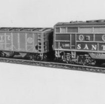 """Image of American Flyer HO """"The Reliable"""" freight set - American Flyer HO train set with Santa Fe, EMD F-3 diesel L3003, NYC covered hopper, Borden milk car and Santa Fe bay window caboose.  Catalog # 30705.   Note that this catalog number was used in 1961 for a similar C&O set.  Included in the set but not shown in the picture was a power pack and track.  This is an A. C. Gilbert catalog photograph.  List price in 1962 was $19.98."""