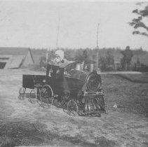 Image of My  favorite toy! - Child riding in a large riding type locomotive with tender. The locomotive resembles those manufactured by Gendron in the early 1900's but may be by others as several small companies manufactured similar locomotives in that period.