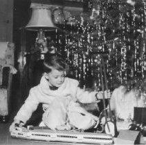Image of Boy w. Streamliner Under Christmas Tree - Young boy plays with Marx M10005 four-unit streamliner train under Christmas tree.