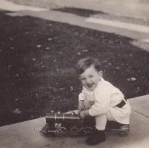 Image of Boy in White on Toy Locomotive - Small boy in white sits on tin toy ride on locomotive.  Dayton toy works Hillclimber locomotive.  Three post cards used the same train, children and or sand box.  See also .114 & .101.