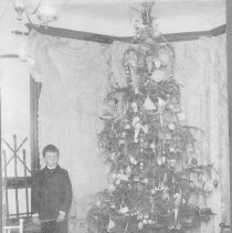 Image of Henry Baker - Young boy stands beside Christmas tree with many toys at base of tree.  See scan of photo back for more information.