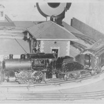 Image of NYC&HRR Locomotive and Passenger Car - NYC&HRR locomotive and passenger car on layout..  Lionel Standard Gauge #5, type 1 steam locomotive with # 19 combine and #124 station.  Also a partial view of powerhouse.  Locomotive 1910 - 1911,  Station 1920-1930 & Powerhouse 1920-1942.