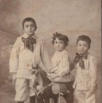 Image of Russian Children w. Toy Horse and Toy Trains - Photo of 3 Russian children.  Middle child sits sidesaddle on horse.  Toy trains and cars on floor.  Cast floor trains of European manufacture.  Also toy truck and a riding horse on wheels.