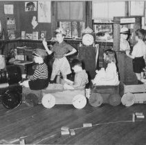 Image of Children Sitting in Home Made Train - Children, in classroom setting, playing railroad sitting in large home made train set made of crates and barrel.
