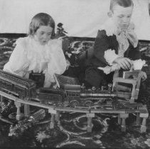 Image of Two Photos of Girl and Boy with Cast Iron Train Set - Two photographs glued on page of photo album and torn out of 