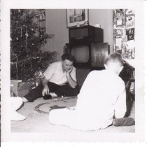 Image of Father & Son Playing with Train Set. - A 3-rail O gauge train set, manufacturer unknown, near a Christmas tree.