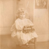 Image of Young Child in Full White Dress with Toy Locomotive on Lap - Consists of 12 B&W prints of various sizes attached to a backboard.  Only one print is train related and that is a 4-1/4 X 5-1/4 one showing a child holding cast iron floor train of European design.