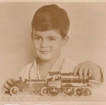 Image of A boy with floor train - A metal floor train and race car.