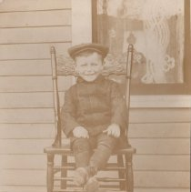 Image of Boy with his prize possession. - Boy sitting on a chair with a Dayton HillClimber type locomotive sitting on the floor.