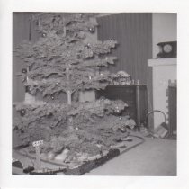 Image of Christmas Scene - Lionel train set, switches and flood light tower under Christmas tree.