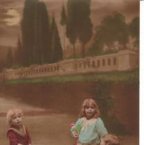 Image of Children with pull toy train. - Three children with a pull toy train.  Three postcards with same children, train and background put in different poses.  See also P2007.212.002 & P2007.212.001.