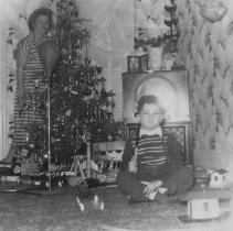 Image of Boy Sitting on Floor w. Toy Train and Punching Bag - Boy sitting on floor in the center of toy train layout. Punching bag and many other toys are around him.  Mother is standing next to Christmas tree.   Trains are a 1469WS Lionel set with 2035 locomotive, an early 6466W whistle tender, 6465 Sunoco double dome tank car, 6257 caboose, 256 freight station and 145 gateman.  Note the early model TV.