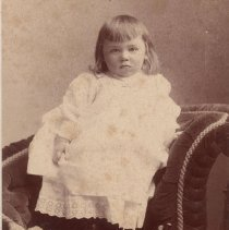 """Image of Child Standing on Chair w. Pull Train on Seat - Child with long hair, about 20 months old, standing on chair with pull train beside him on seat of chair.   Boy is holding an Ives #185 steam locomotive.  This is identified as his #755 in Rick Ralston's book """"Cast Iron Floor Trains"""".  Pictured in a velvet chair with a carved wooden horse.  No tender is shown for the locomotive, which was not offered until the 1904 catalog."""