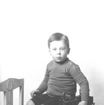 Image of My Pride & Joy - Boy sitting on a table with a large scale locomotive which may be a pull toy type.  It is of a European protoype.
