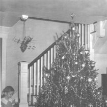 Image of Young Girl on Stairs by Christmas Tree w. Toy Trains - Photograph of small girl sitting on stairs next to Christmas tree with toy train under tree.  One train is a Lionel O27 gauge #1074W Passenger outfit with #1669 type II locomotive, #1690 Pullman cars (2) & #1669 Observation car.
