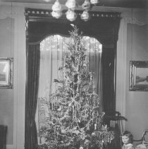 Image of Christmas 1918 w. 2 Children - Two young children stand beside Christmas tree with circle of standard gauge track under tree.  Unidentified Steam locomotive.