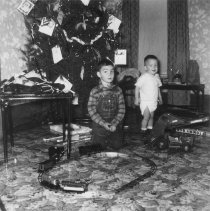 Image of Christmas Photo w. Boy and Baby w. Toy Train on Floor - Photograph of young boy in overalls and baby in diapers in front of Christmas tree with Marx electric toy train set on floor.