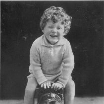 Image of Dutch Postcard of Small Boy on Large Ride-On Locomotive - Young boy with curly hair sits on ride-on locomotive.  Locomotive appears to be of mostly wooden construction, may be home made.