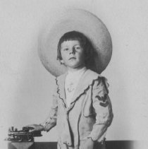 Image of Boy in Wide-Brimmed Hat and Sailor Suit w. Toy Locomotive - J.E. Allen, young boy, stands in wide-brimmed hat and sandals with cast iron toy floor train on ledge behind him.