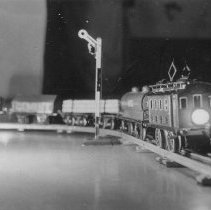 Image of European Toy Train - Very small photo of European toy train.  Train is a Marklin #RS1290 locomotive, #1804 log trucks, #1921 gondola, #1919 cement car and an oil car.  All c. 1928-29.