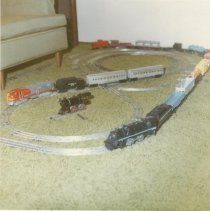 Image of Toy Trains on Track on Floor - Trains are a Marx Santa Fe passenger set and a Lionel Scout freight set with a #247, B&O blue strip locomotive.  Shown on an oval and figure 8 track setup.  Part of a 3 picture set, others are P2003.11.91 & 93.  Also shown is a Bavarian cast iron clockwork locomotive.  See second image of print back for more info.