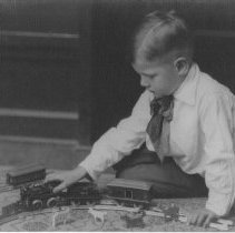 Image of Boy Sits on Floor with Train Set - Small boy in scarf and white shirt sits on floor playing with train set and animals.  Ives clockwork #2 locomotive, #11 tender, #550 baggage car.  The passenger car in the background is not a part of the Ives set. c. 1915