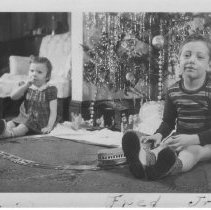Image of Edith and Fred Jr. under Christmas Tree with Toy Train