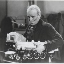 Image of Thunder with Lon Chaney Sr. - Film still of Lon Chaney holding a large (Pacific type) toy locomotive in the movie, Thunder, 1929.