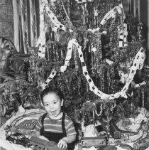 Image of Baby Boy at Christmas holding Plastic Locomotive, Unique Art #600 in background - Photograph of young boy holding large plastic toy train under Christmas tree.  Train set under tree is a Unique Art Manufacturing Company, Inc. #600 clockwork train set.