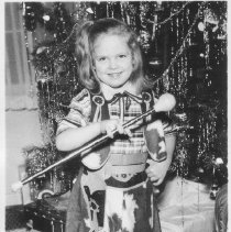 Image of Young Girl in Cowgirl Outfit with Toy Train under Christmas Tree - Young girl in cowgirl outfit with Marx M10005 toy train under Christmas tree