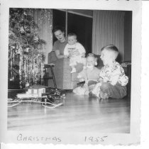 Image of Mother & 3 Children Watching Toy Train under Christmas Tree - Photo of mother and 3 children watching toy train under Christmas tree.