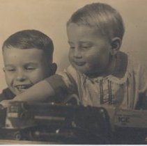 Image of Two Smiling Children Play with Lionel Trains - 1940s era photograph.  Large photo of two children playing with Lionel trains