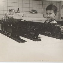 Image of Young Boy with Lionel Trains Displayed on Track - Young boy stands behind table where Lionel trains are displayed on track.  Pictured are a Lionel 2020, 2025, NW-2 and some box cars.